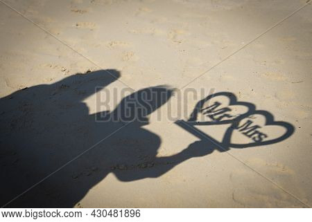 Abstract Silhouette Shadow On Sandy Beach Of Couple Holding Mr And Mrs Sign On Wedding Day