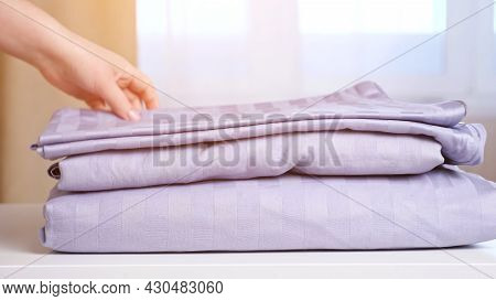 Skilled Housemaid Puts Different Clean Folded Knitwear Clothes In Pile On White Table Against Large