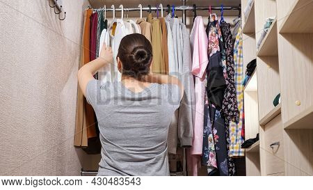 Young Woman In Grey T-shirt With Hair Bun Chooses Clothes Hanging On Metal Bar In Contemporary Walk-