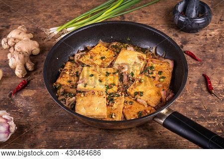 Stewed Tofu In A Spicy Sauce With Onions, In A Frying Pan On A Rustic Wooden Table, Close-up
