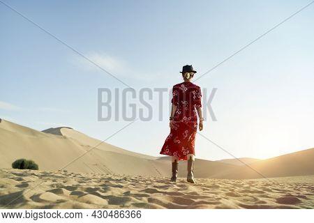 Rear View Of An Asian Woman Walking In Desert Under Blue Sky