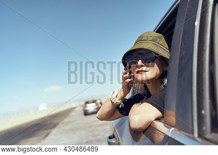 Asian Woman Traveler With Hat And Sunglasses Sticking Head Out Of Rear Window Of Car Looking At View