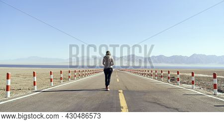 Rear View Of An Asian Woman Tourist Walking On An Empty Highway Towards A Lake