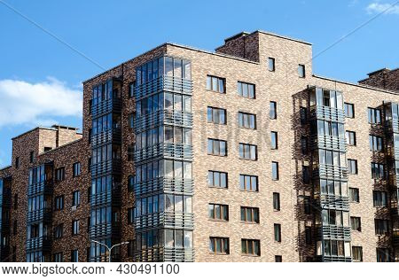 Realty.  Multistorey Residential Building Made Of Variegated Multicolored Bricks With Glazed Balconi
