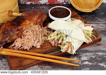 Aromatic Half Crispy Duck With Chinese Style Pancakes, Spring Onions And Hoisin Sauce On A Wooden Bo