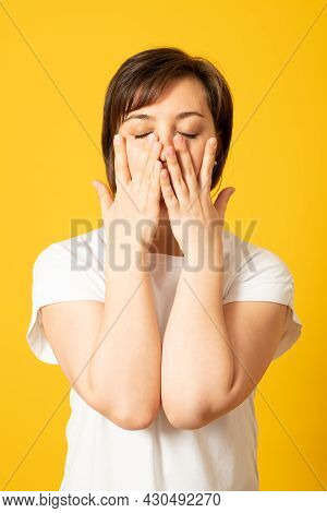 Disappointed Dejected Female Wearing White Loose T-shirt Covering Her Face With Hands Being Tired An