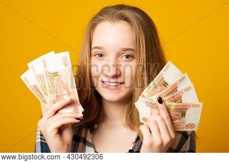 Happy Beautiful Young Girl Holding Rubles Money On Yellow Background. Sale, Finance, Banking, Winnin
