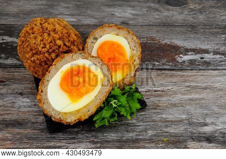 Two Scotch Eggs One Cut In Half Showing Orange Yolk And Pork Sausage Meat