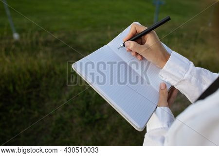The Girl Writes Down Ideas In A Notebook. The Girl Makes Notes In A Notebook While In Nature. A Chec