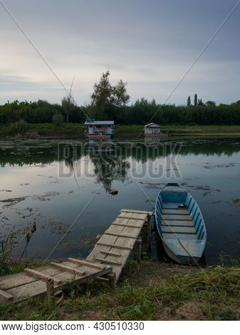 Landscape Of Sava River With Fishing Boats And Huts During Summer Overcast Day