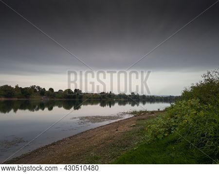 Landscape Of Sava River During Cloudy Day With Gray Moody Clouds In Long Exposure