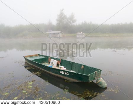 Landscape With Sava River And Moored Boat In Water And Fishing Huts In Fog During Foggy Autumn Morni