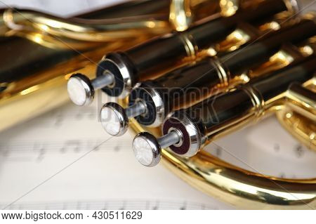Close Up Of Valves Of A Brass Tenor Horn Musical Instrument Lying On Sheet Music