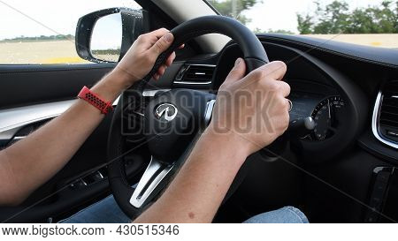 Unrecognizable Man Holding Hands On Steering Wheel Of Infiniti Qx50 And Driving Car At Highway. Dash