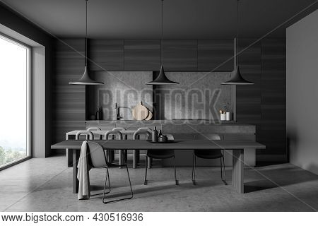 Dark Kitchen Room Interior With Dining Table, Twelve Chairs, Concrete Floor, Electric Cooker And Pan