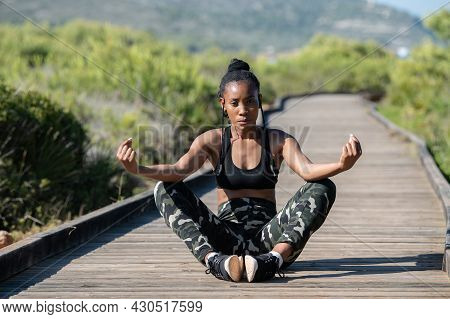 Calm Afro American Woman In A Meditation Pose On A Wooden Runway Outdoors: Meditation And Well-being