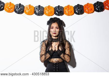 Image Of Scared And Worried Asian Woman In Witch Costume Looking Concerned, Wearing Witch Costume An