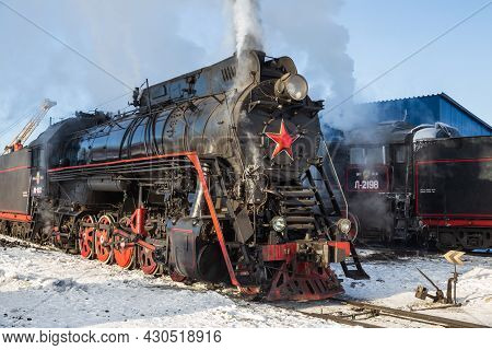 Sortavala, Russia - March 10, 2021: Old Steam Locomotive Pump Out Clouds Of White Smoke At Sortavala