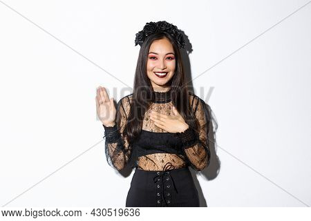 Image Of Cute Sincere Asian Girl In Halloween Costume Making Promise, Holding One Hand On Heart Whil