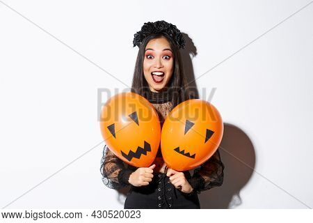 Image Of Asian Girl In Evil Witch Costume Holding Two Orange Balloons With Scary Faces, Celebrating