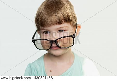 A Pretty Funny Little Girl With Glasses On Her Nose On A Light Background. A Contented Child With Gl