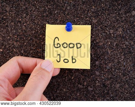A Woman Holding An Adhesive Note With The Words Good Job On It Pinned On A Cork Bulletin Board. Clos