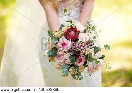 Bride In A Dress Standing In A Green Garden And Holding A Wedding Bouquet Of Flowers And Greenery. W
