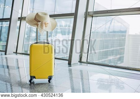Yellow Suitcase And Straw Women's Hat In Airport Departure Lounge On Airplane Background. Travel And
