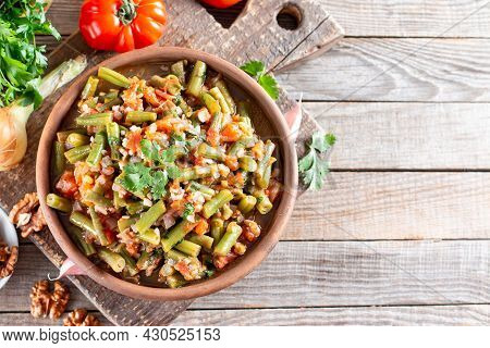 Tomato Lobio Of Green Bean Pods In A Bowl On A Wooden Background. Lenten Dish. Flat Lay, Top View Wi