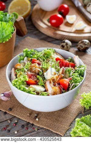 Caesar Salad With Smoked Chicken And Parmesan On A Plate On A Wooden Table
