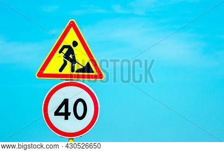 Road Sign: Speed Limit 40 Km/h In Combination With Road Works Ahead. Road Sign Against A Blue Sky
