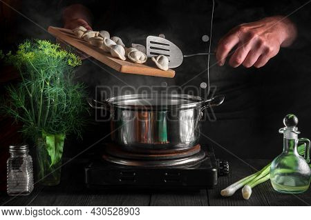 Professional Chef Cooks Dumplings In A Saucepan In The Restaurant Kitchen. Close-up Of Hands Of The