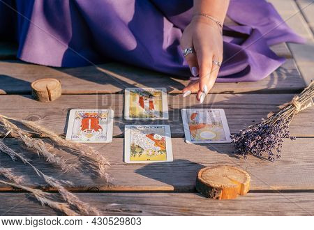 Woman's Hand With Purple Nails Points To Four Tarot Cards Spread Out On Wooden Surface Next To Spike