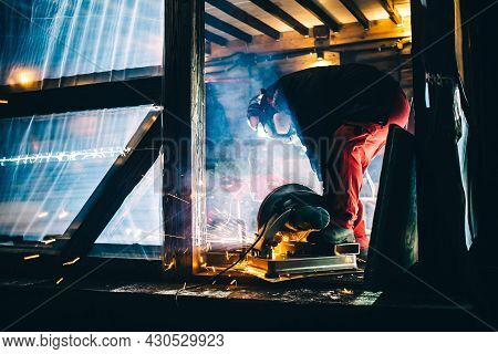 A Man Is Sawing Metal Pipes On A Plunge-cut Miter Saw. Sparks Is Flying From Under The Disc. The Wor