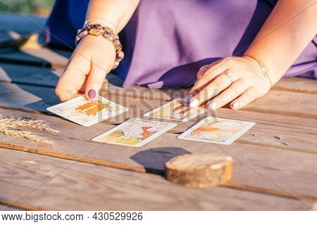 Woman's Hand With Purple Nails Lays Out One Of Four Tarot Cards Spread Out On Wooden Surface Next To