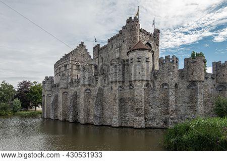 Gent, Flanders, Belgium - July 30, 2021: West Side Of Gray Gravensteem Medieval Stone Castle Under B