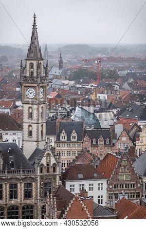 Gent, Flanders, Belgium - July 30, 2021: Slender Postal Clock Tower Over Dense Cityscape In The Rain