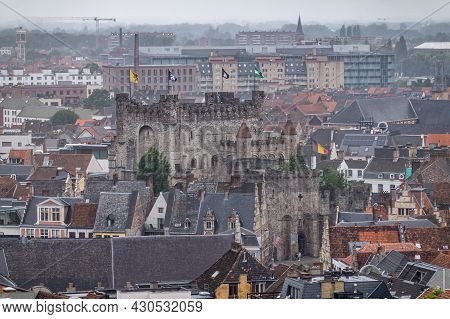 Gent, Flanders, Belgium - July 30, 2021: Dark Gray Gravensteen Stone Castle And Its Many Flags Surro