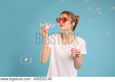Young Woman Blowing Soap Bubbles On Light Blue Background