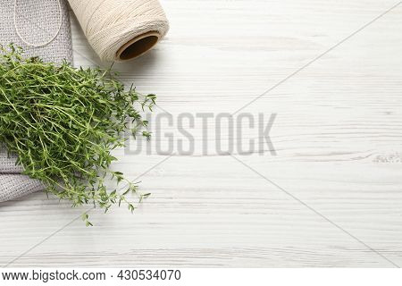 Bunch Of Aromatic Thyme, Napkin And Twine On White Wooden Table, Flat Lay. Space For Text