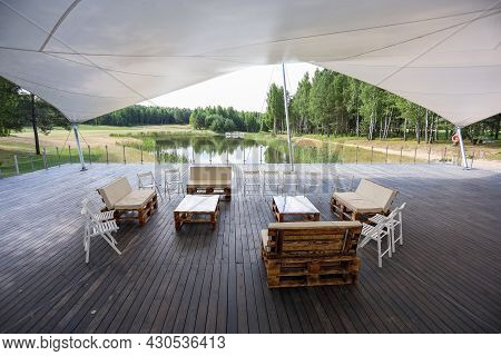 Wooden Furniture In A Tent In The Middle Of The Green Field. High Quality Photo