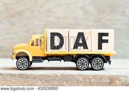Toy Truck Hold Alphabet Letter Block In Word Daf (abbreviation Of Delivered At Frontier) On Wood Bac