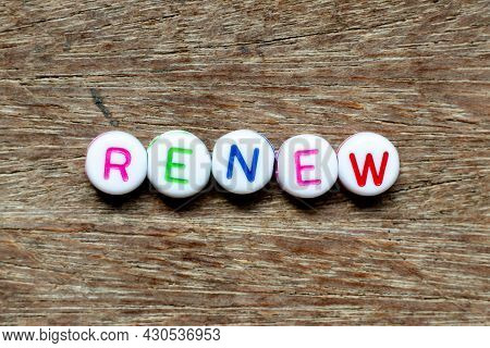 White Bead With Color Letter In Word Renew On Wood Background