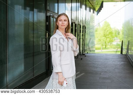 Smiling Woman In Casual Clothes Standing By The Office. Business Woman With A Mobile Phone In Her Ha