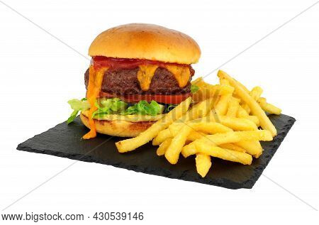 Cheeseburger And French Fries In A Brioche Bread Roll On A Slate Serving Board