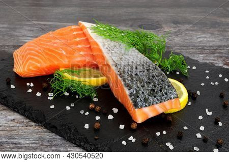 Two Fresh Raw Salmon Fillets With Dill Herb Garnish And Lemon Slices On A Slate Serving Board