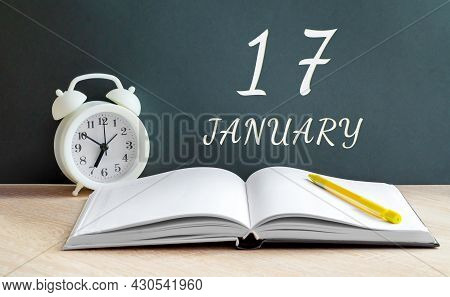 January 17. 17-th Day Of The Month, Calendar Date.a White Alarm Clock, An Open Notebook With Blank P