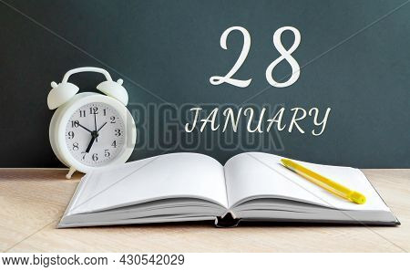 January 28. 28-th Day Of The Month, Calendar Date.a White Alarm Clock, An Open Notebook With Blank P