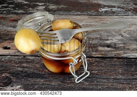Glass Storage Jar Filled With Pickled Onions In Malt Vinegar On A Rustic Wood Background