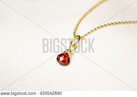 Golden Necklace With The Stone Of The Chestnut Brown On White Background.close Up.